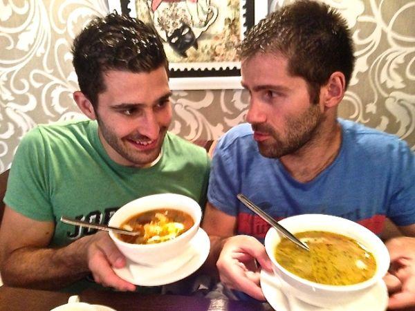 Stefan eating solyanka soup and Sebastien with ukha soup