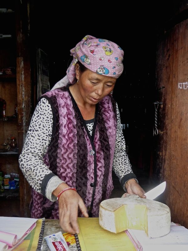 Old lady cutting some yak cheese at Chitre village
